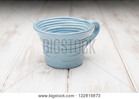 Blue Teacup On A White Wooden Panel Surface
