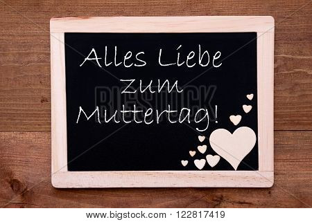 Blackboard With German Text Alles Liebe Zum Muttertag Means Happy Mothers Day. Brown Wooden Hearts. Wooden Background With Vintage, Rustic Or Retro Style.