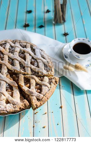 Baked homemade rustic apple tart pie with cutted piece in ceramic dish next to a cup of coffee white napkin with anice cinnamon in glass jar on the background over wooden turquoise table natural side sunlight selective focus