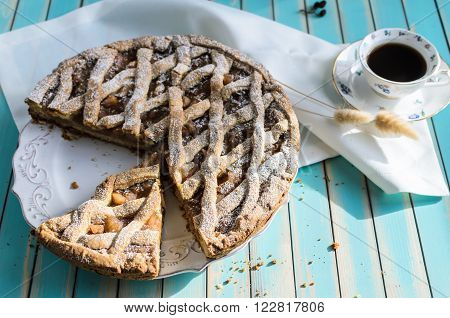 Baked homemade rustic apple tart pie with cutted piece with crumbs in ceramic dish next to a cup of coffee and white napkin over wooden turquoise table background with natural side sunlight selective focus