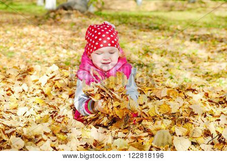 Little happy girl playing with fallen golden leaves