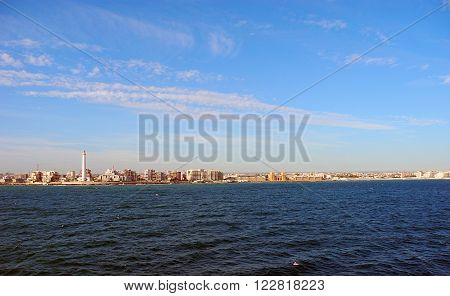 View from the sea to the lighthouse and the architecture of the city of Bari.