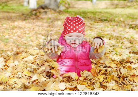 Little  girl playing with fallen golden leaves