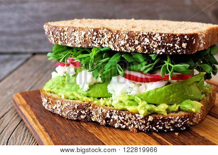 Superfood Sandwich With Whole Grain Bread, Avocado, Egg Whites, Radishes And Pea Shoots On Wood Boar