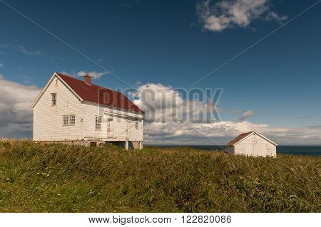 old wooden fishermen house and shed with red roofs in Longue-Pointe-de-Mingan Quebec Canada