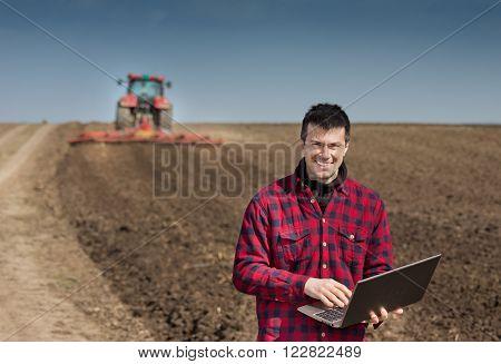 Farmer With Laptop On The Farmland