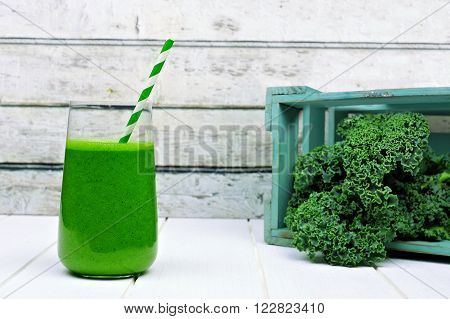 Green Kale Smoothie In A Glass With Crate Of Kale Against Rustic White Wood In Background