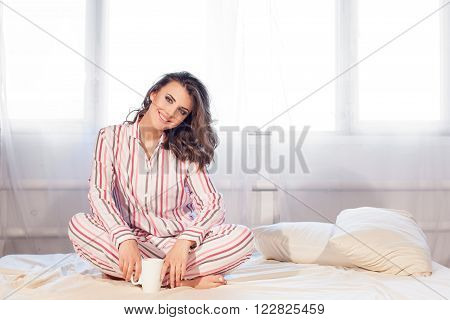 girl in pajamas woke up in the morning at the window