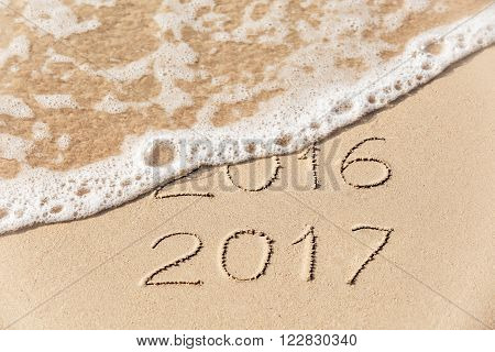 2016 2017  inscription written in the wet yellow beach sand being washed with sea water wave. Concept of celebrating the New Year at some exotic place.