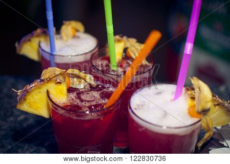 Four red fresh longdrinks served with ananas