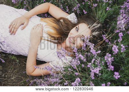 pregnant nice woman girl lies in Lavender