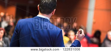 Rear view of speaker giving a talk on corporate Business Conference. Audience at the conference hall. Business and Entrepreneurship event. Panoramic composition. ** Note: Visible grain at 100%, best at smaller sizes