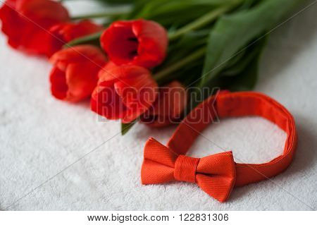 bouquet of red tulips and a red bow tie.