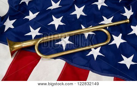 A brass bugle on a old  American flag.