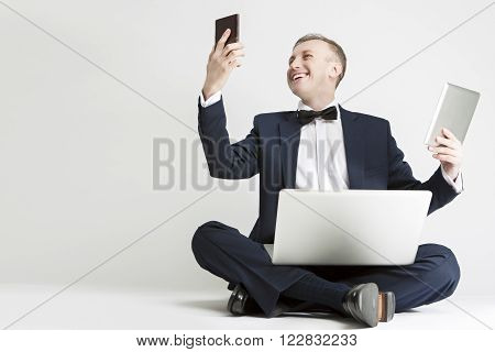 Portrait of Smiling Handsome Caucasian Man in Suit Using Digital Pad, Smartphone and Laptop for Multiple Communication. Horizontal  Image Orientation