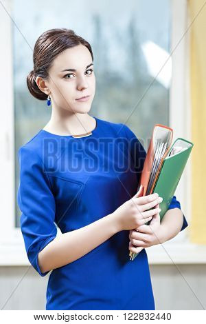 Business Concepts and Ideas. Portrait of Positive Caucasian Brunette Female Posing Indoors With Stack of Folders. Vertical Shot