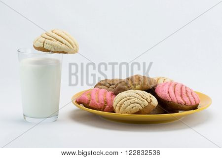 A glass of milk next to a plate of concha bread
