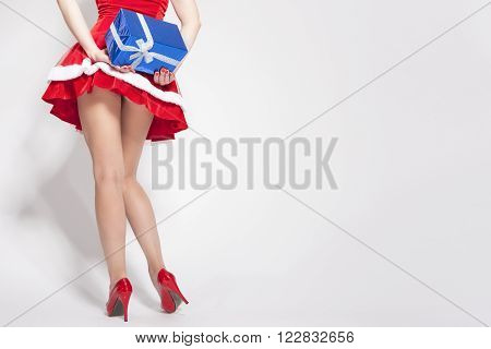 Hot and Sexy Caucasian Female Tanned Legs. Holding Gift Box Behind. Isolated on White. Horizontal Shot