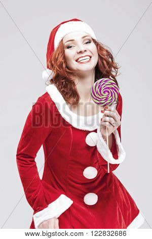 Happy Alluring Caucasian Red haired Santa Helper with Color Sweet Lollipop Sugar-Plum Candy. Vertical Image