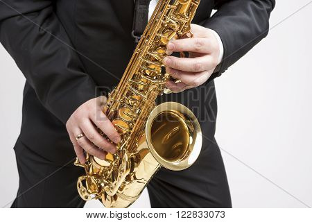 Music Concept. Closeup of Hands of Saxophone Player Playing on Saxophone Against White.Horizontal Image