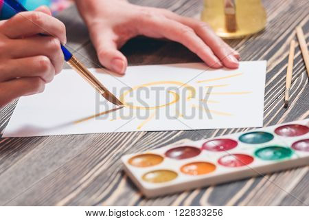 Close up section of female painter artist - hand leading brush. Woman painting a picture on wooden table