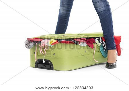 Crowded suitcase between female legs. White background.