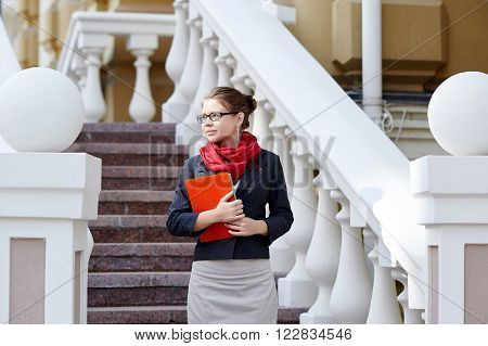 Young business woman hold in hand folder against office building on street near stairway.