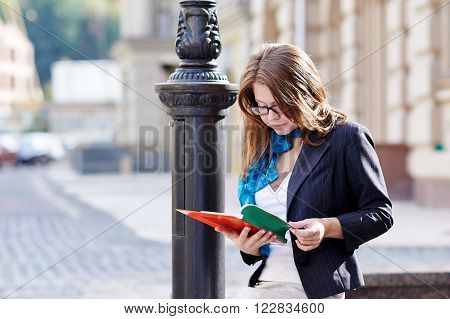 Beautiful woman student in glasses reading book.