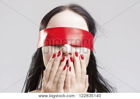 Surprised Brunette Caucasian Female with Eyes Binded with Red Lace Ribbon. Posing With Hands Closing Mouth. Horizontal Image