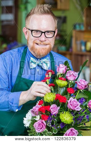 Dapper man wearing eyeglasses and apron creating a flower arrangement