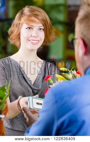 Teen customer in a busy flower shop using electronic coupon