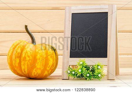 pumpkin with a blank chalk board for your text in wood room.
