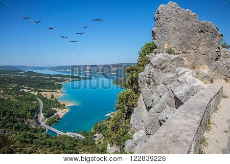 Canyon of Verdon, Provence, May. Bridge on the lake with turquoise water.  The migrating cranes over lake