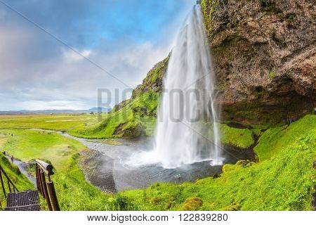 Seljalandsfoss waterfall in July. Large rainbow decorates a drop of water. The warm July day in Iceland