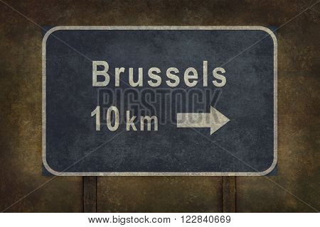 Distressed Brussels road sign with arrow illustration with ominous background