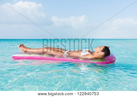 Beach sexy woman relaxing during suntan sunbathing on floating pink pool inflatable plastic air mattress float in pristine turquoise ocean water background at luxury destination getaway.