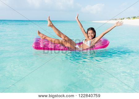 Beach fun girl playful on pink pool float mattress floating on ocean water vacation getaway. Party woman cheering legs and arms up on inflatable toy bed swimming in turquoise sea.