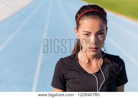 Runner woman listening to music with earphones for running motivation getting ready to race. Asian female athlete training focus, determination and cardio on athletic tracks at stadium.