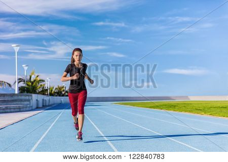 Female Asian athlete runner running on blue tracks at outdoor stadium in summer. Sporty woman jogging listening to music with earphones training cardio for weight loss success. Wellness and health.