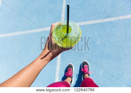 Runner drinking a healthy spinach green smoothie on outdoor running track getting ready for run. Closeup of hand holding juice drink on blue lane, social media health and fitness concept.