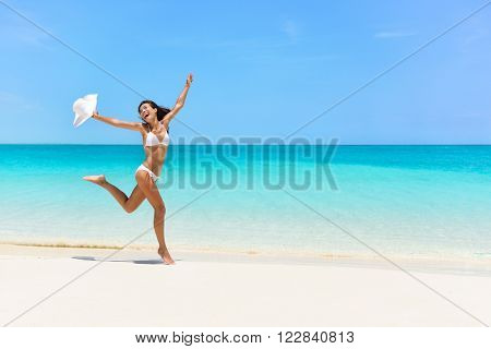 Happy bikini woman jumping of joy and success on perfect white sand beach on caribbean tropical vacation. Holiday girl with sexy slim suntan body running of freedom and happiness.