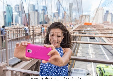 Happy New York City selfie tourist young woman taking a self-portrait photo with smartphone app on Brooklyn Bridge, NYC, Manhattan, USA. Asian girl doing mobile phone photography for social media.