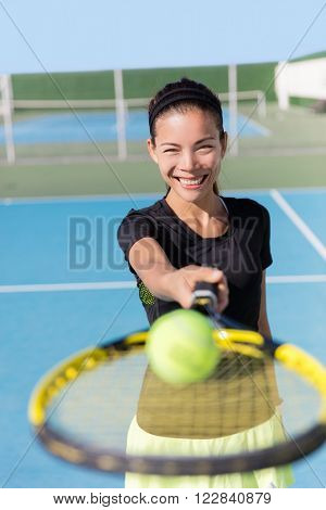 Tennis girl holding racket and ball on court. Asian woman sport athlete showing sports equipment on outdoor summer club for fitness workout. Attractive ethnic person smiling.