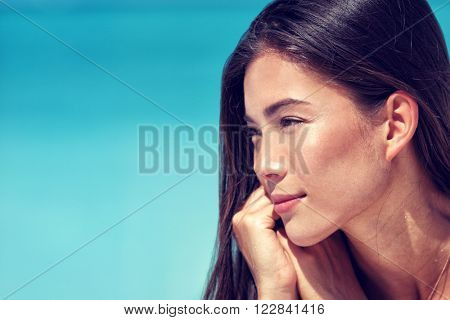 Young Asian beauty woman face closeup portrait. Mixed race Chinese Caucasian girl profile with healthy glowing skin and natural makeup on cheeks, eyelids, eyebrows, lips. Skincare concept.