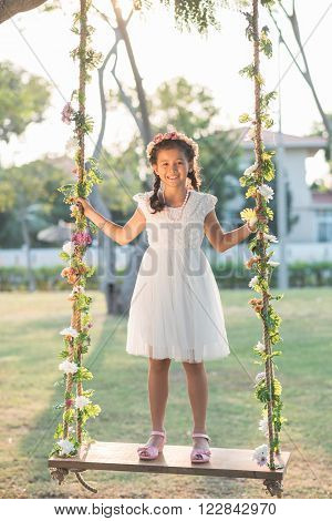 Happy preteen in wreath and beautiful dress standing on swing