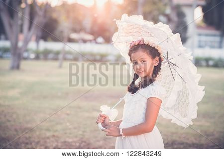 Beautiful preteen girl with white lace umbrella looking at camera