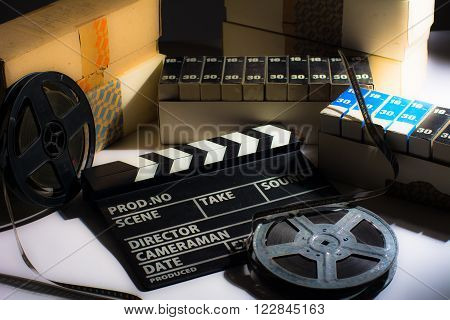 Reel with film and cinema clap. Motion picture films in boxes