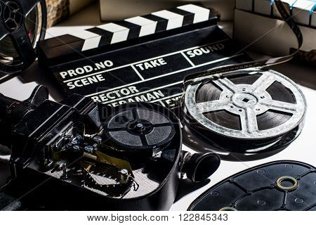 Reel with film and cinema clap. Film boxes. Open the lid cameras