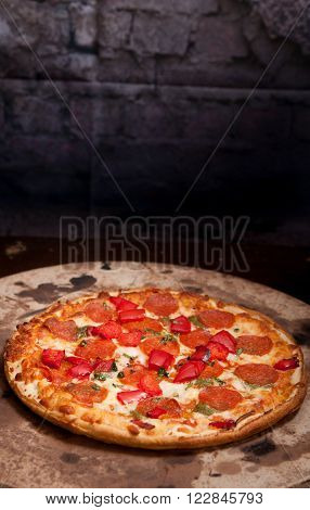 thin crust pepperoni pizza with red peppers on a pizza stone