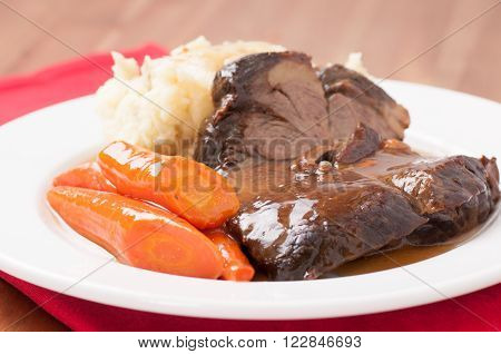 delicious braised beef roast with creamy mashed potatoes and roasted carrots and rice gravy
